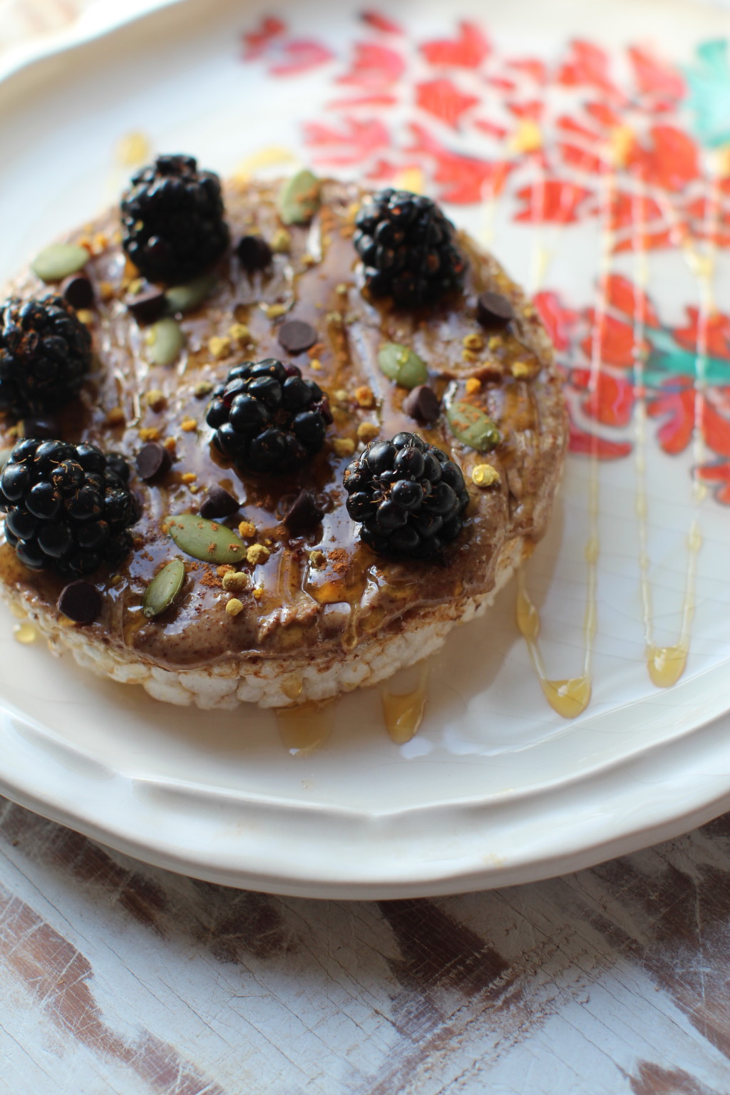 Rice cracker with almond butter, honey, bee pollen, cinnamon dust, pepitas, black berries and chocolate chips
